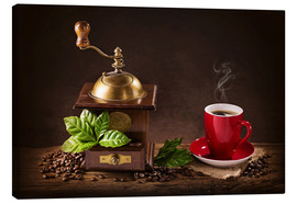 Stampa su tela  Coffee mill with beans and green leaves and a cup of coffee - Elena Schweitzer