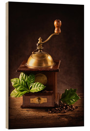 Legno  Coffee mill with beans and green leaves and a cup of coffee - Elena Schweitzer