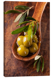 Stampa su tela  Spoon with green olives on a wooden table - Elena Schweitzer